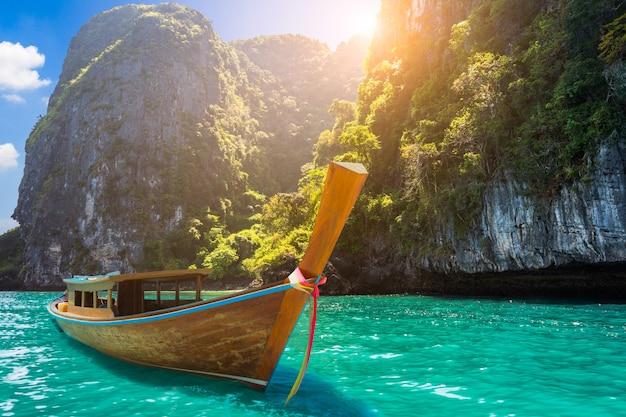 Boot des langen schwanzes auf tropischem meer in krabi thailand mit sonnenuntergang und berg Premium Fotos