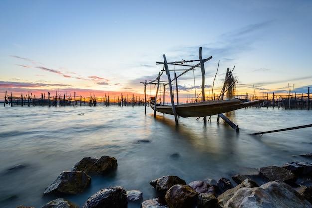 Boot des langen schwanzes im meer mit felsen auf sonnenunterganghimmel Premium Fotos