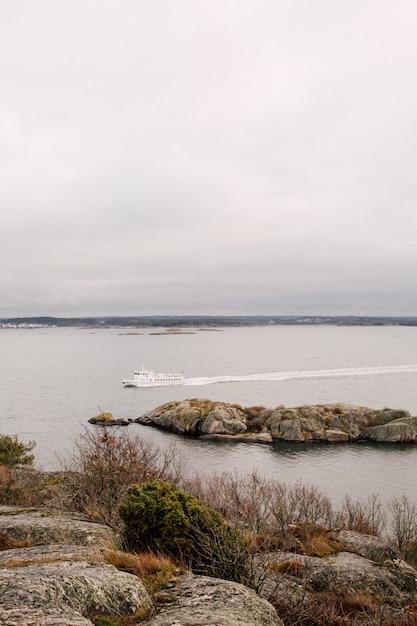Boot segeln auf dem meer unter bewölktem himmel Kostenlose Fotos