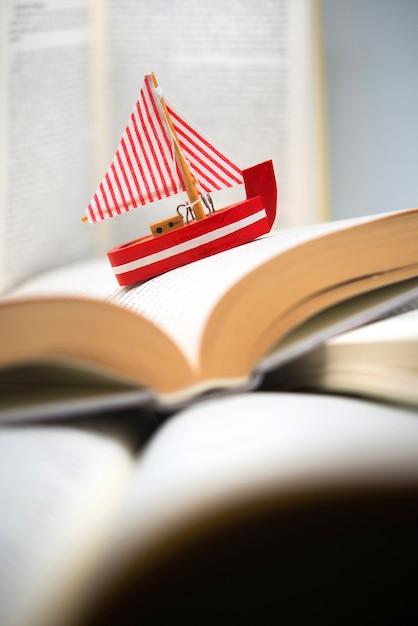 Boot zwischen büchern navigieren, reisen, lesen, abenteuer in büchern Premium Fotos