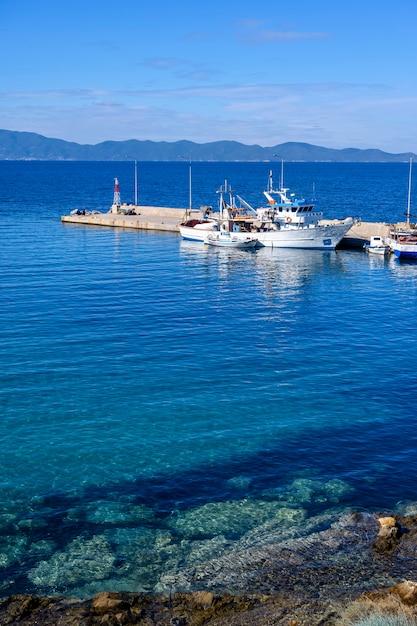 Boote im hafen von nea roda auf blauem meerwasser, chalkidiki, griechenland Premium Fotos