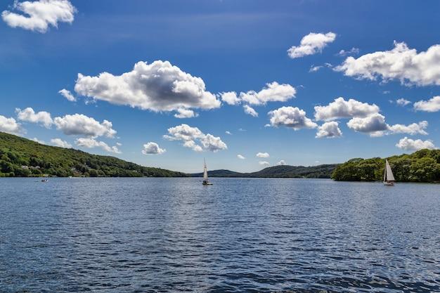 Boote im windermere see mit kleinen, flauschigen wolken darüber Kostenlose Fotos