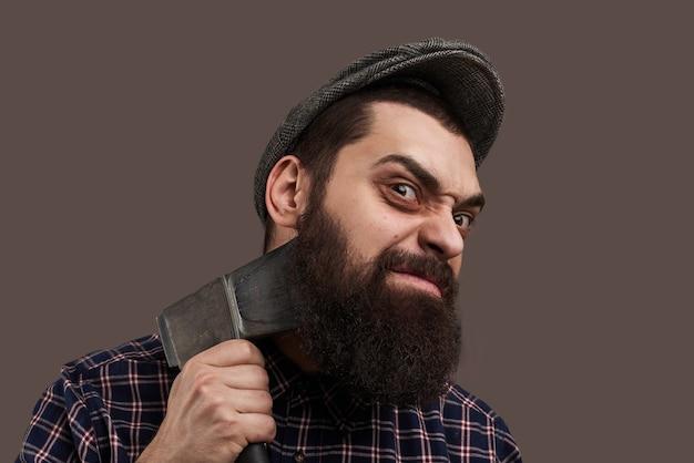 Boshafter brutaler bärtiger mann, der sich mit axt rasiert. porträt des hipsters mit bart. heißes männliches konzept. verrückte emotionen im gesicht. Kostenlose Fotos