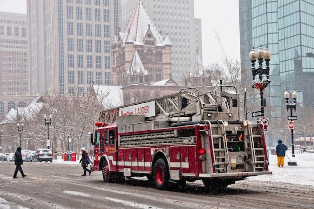 Boston, massachusett - 16. januar 2012: feuerwehrauto, welches die schneebedeckten straßen der stadt reist. Premium Fotos