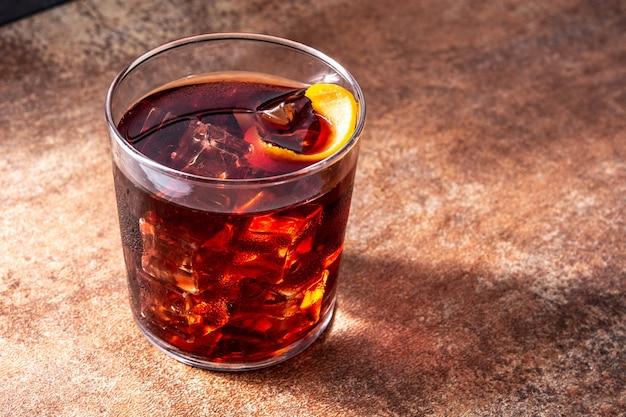Boulevardier cocktail und orangenschale auf holztisch. Premium Fotos