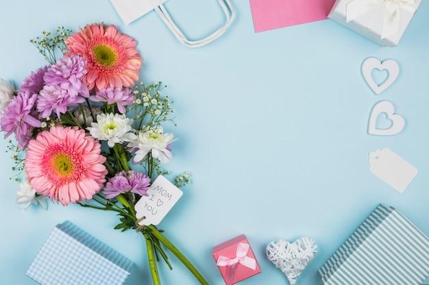Bouquet von frischen blumen mit titel auf tag in der nähe von paket, geschenkkartons und dekorationen Kostenlose Fotos