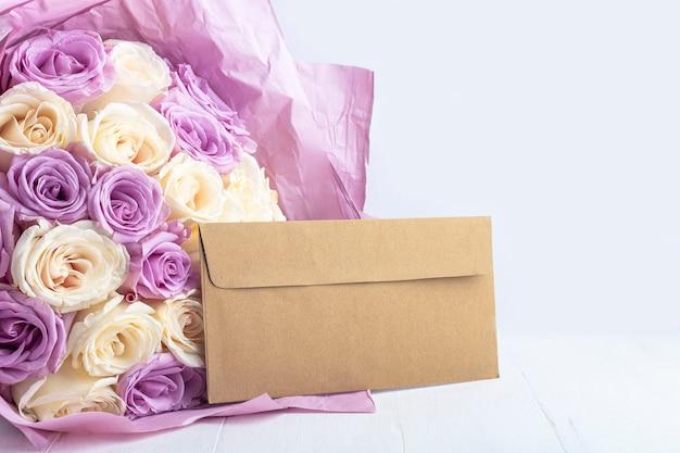 Bouquet von frischen erstaunlichen weißen und lila rosen und bastelumschlag. geschenk für urlaub mutter, valentinstag, geburtstag, jubiläum und hochzeit. geschenkverpackung conceptr text. Premium Fotos