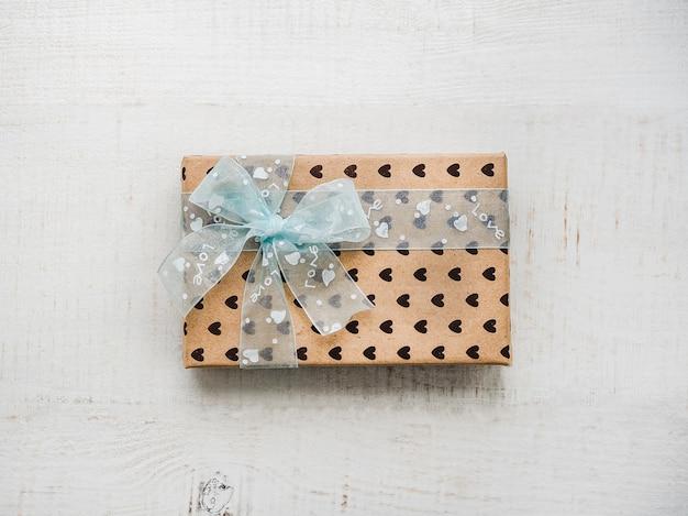 Box mit einem geschenk, mit einem band gebunden, hinweis mit süßen worten Premium Fotos