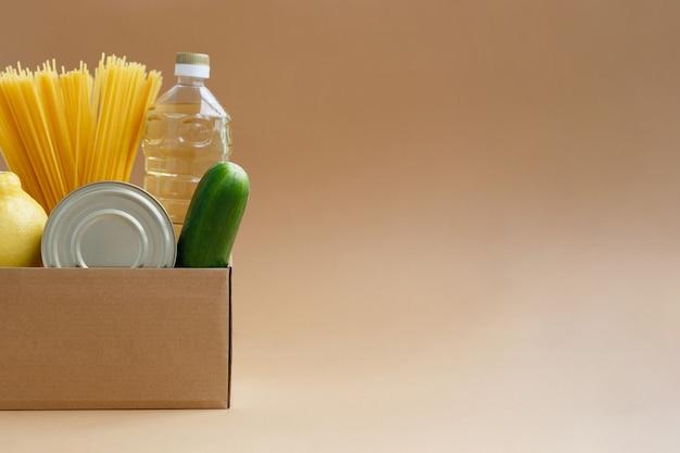 Box mit einem vorrat an lebensmitteln. spende von produkten für bedürftige. obst und gemüse, dosen und nudeln Premium Fotos