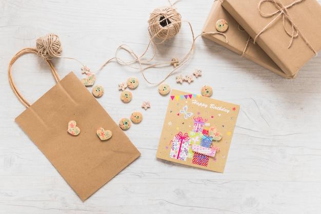 Boxen; fadenspule; einkaufstaschen aus papier; knöpfe und geburtstagsgrußkarte auf weißem strukturiertem hintergrund Kostenlose Fotos