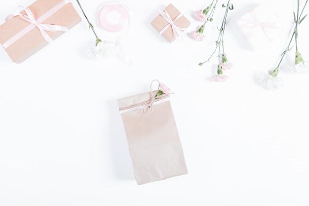 Boxen mit geschenken, bändern, papiertüte und blumen auf weißem tisch, draufsicht Premium Fotos