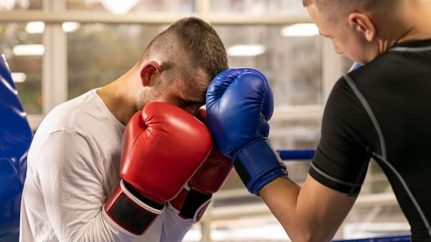 Boxer mit handschuhen, die mit mann im ring trainieren Premium Fotos