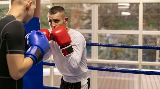 Boxer mit helm und handschuhen trainieren mit mann Premium Fotos