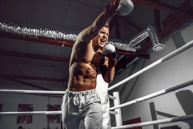 Boxer. überzeugter junger boxer auf dem boxring Premium Fotos