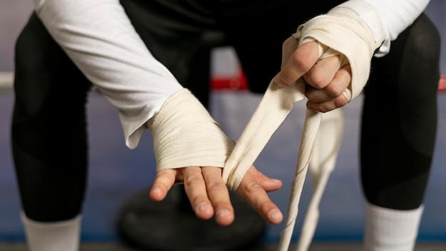 Boxer wickelt seine hände, bevor er im ring trainiert Kostenlose Fotos