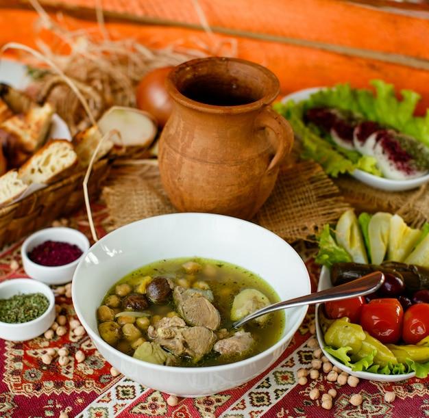Bozbash-schüssel-aserbaidschanerfleischeintopfgericht diente mit essiggurken und brot Kostenlose Fotos
