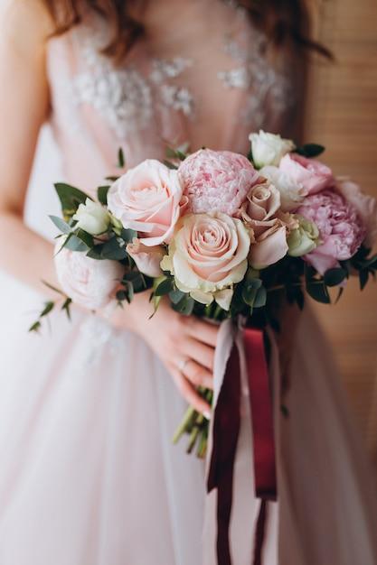 Bräute, die blumenstrauß mit pfingstrosen, freesie und anderen blumen in den händen der frauen heiraten. licht und lila frühlingsfarbe. morgen im zimmer Premium Fotos