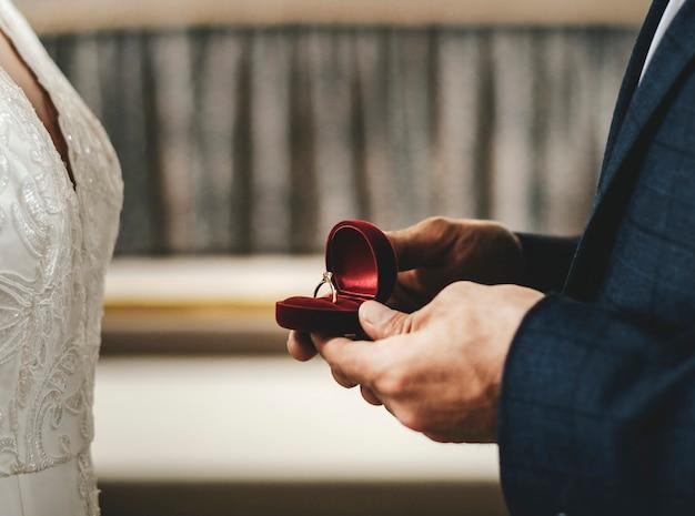 Bräutigam, der einen kasten mit dem ehering hält Premium Fotos