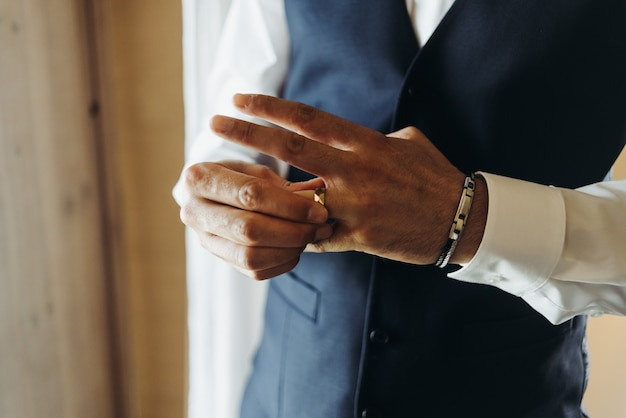 Bräutigam hält den ehering, der vor dem fenster in einem hotel r steht Kostenlose Fotos