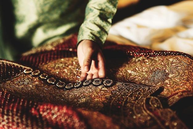 Bräutigam im grünen hemd berührt sein rotes sherwani Kostenlose Fotos