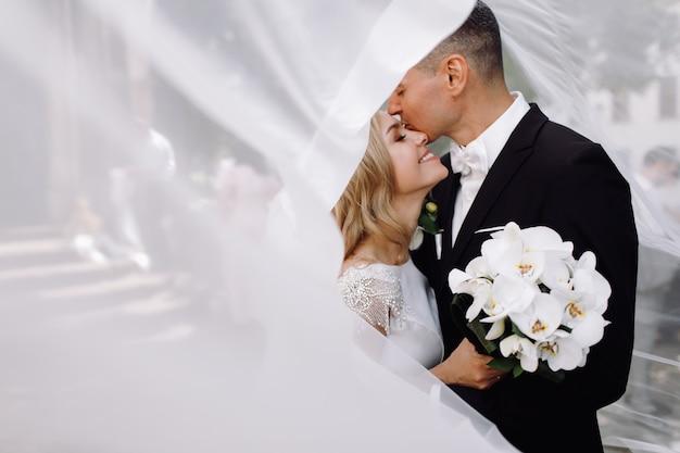 Bräutigam im schwarzen smoking umarmt zarte erstaunliche braut, während sie stehen Kostenlose Fotos