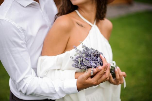Bräutigam im weißen hemd, das braut im weißen kleid mit blumenstrauß von blumen umarmt Premium Fotos