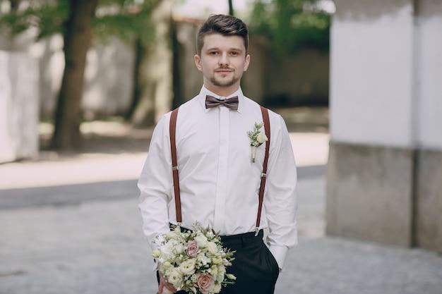 Bräutigam in strapsen mit einem blumenstrauß Kostenlose Fotos