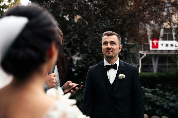 Bräutigam lächelt draußen und rückansicht der braut Kostenlose Fotos