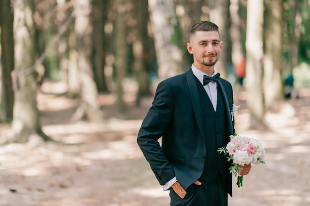 Bräutigam mit blumenstrauß, der im freien aufwirft Premium Fotos