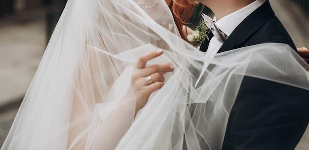 Bräutigam trägt charmante braut auf seinen armen Kostenlose Fotos