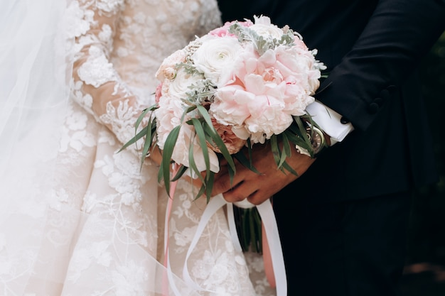 Bräutigam und braut halten hochzeitsrosa-blumenstrauß
