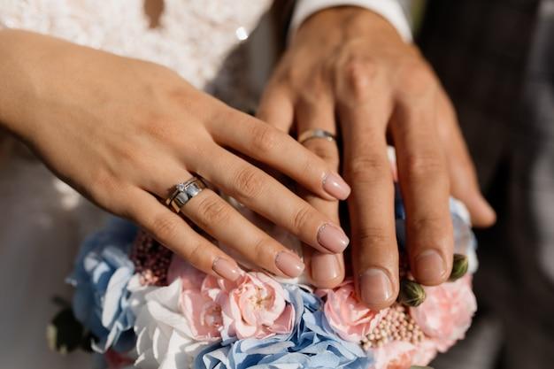 Bräutigam und braut legen ihre hände auf die blumen Kostenlose Fotos