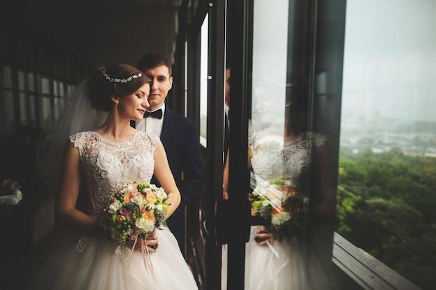 Bräutigam und braut mit einem blumenstrauß, der auf terrasse mit grüner naturansicht steht Premium Fotos