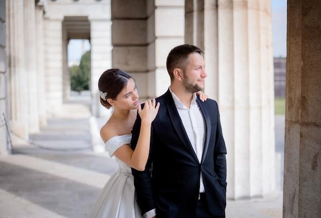 Bräutigam und braut stehen an dem warmen, sonnigen tag in der nähe der riesigen säule Kostenlose Fotos