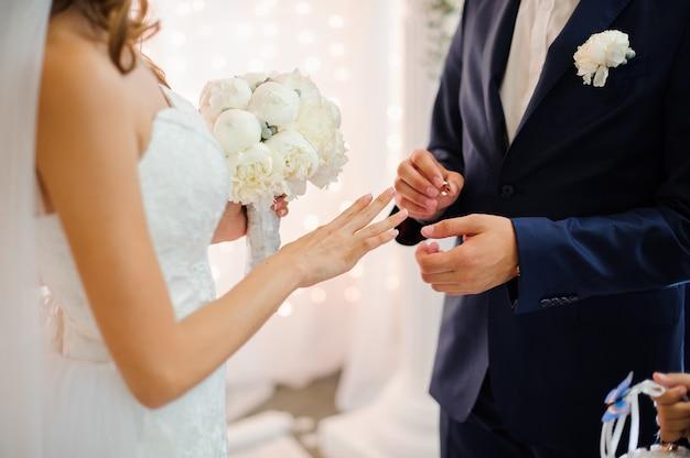 Bräutigam zieht einen goldenen ehering am finger einer schönen braut an Premium Fotos