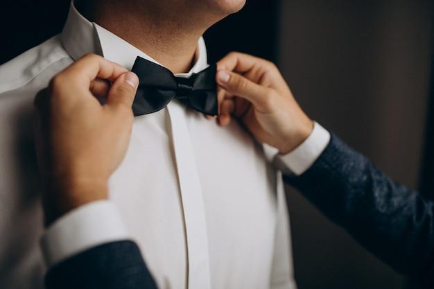 Bräutigam zieht sich vor der hochzeitszeremonie an und verbeugt sich Kostenlose Fotos