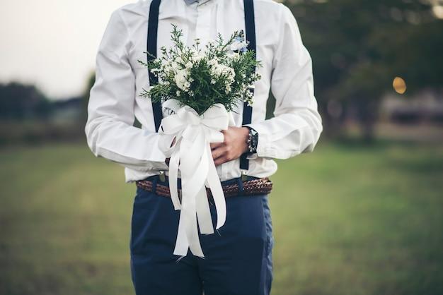 Bräutigamhand, die blume der liebe im hochzeitstag hält Kostenlose Fotos