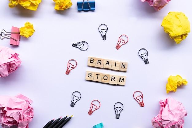 Brainstrom-konzept, wort auf dem holzklotz umgeben durch zerknitterte papiere und papierklammer der glühlampe Premium Fotos