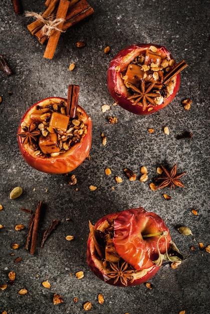 Bratäpfel gefüllt mit müsli, toffee und gewürzen auf schwarzem steintisch Premium Fotos