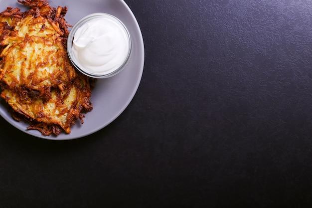 Bratkartoffel und sauerrahm auf einer platte auf einem dunklen steinhintergrund Premium Fotos