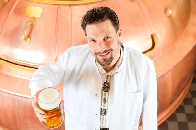 Brauer mit bierglas in der brauerei Premium Fotos