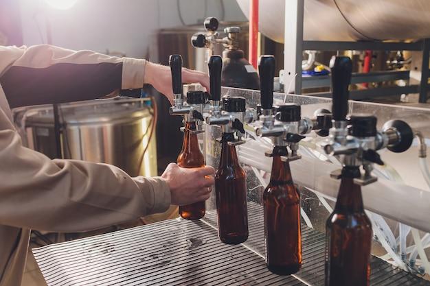 Brauereifabrik, die bier in glasflaschen auf fördererlinien verschüttet. industriearbeit, automatisierte produktion von lebensmitteln und getränken. technologische arbeit in der fabrik. Premium Fotos