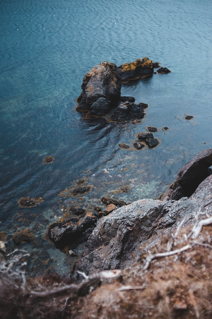 Braune felsformation auf blauem meerwasser während des tages Kostenlose Fotos