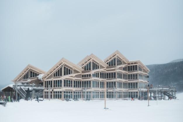 Braune holzhäuser auf schneebedecktem boden während des tages Kostenlose Fotos