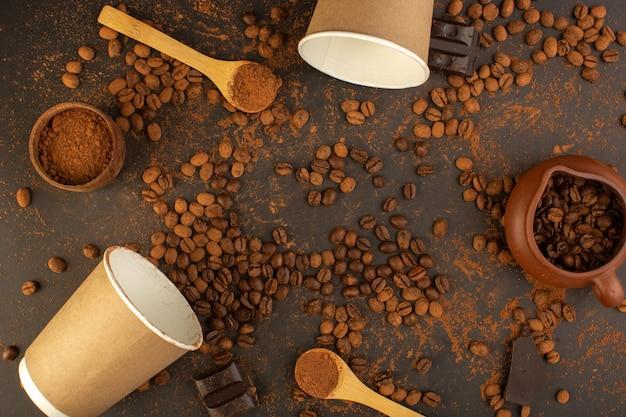 Braune kaffeesamen von oben mit schokoriegeln und kaffeetassen Kostenlose Fotos