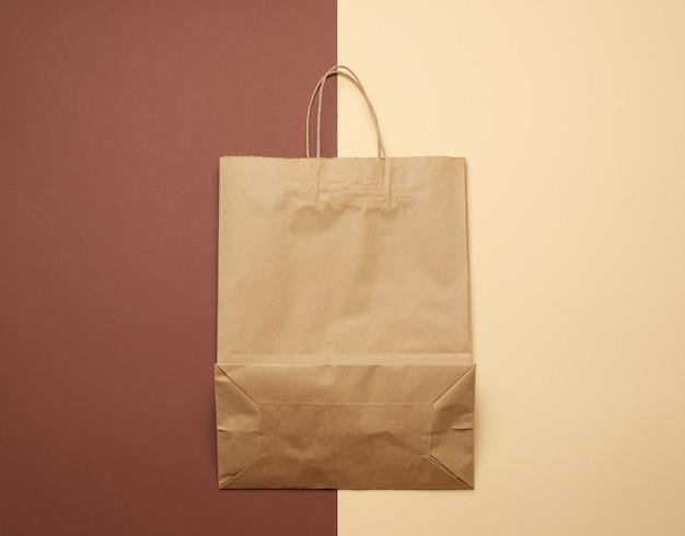 Braune papiertüte mit griffen zum einkaufen auf einem braunen hintergrund Premium Fotos