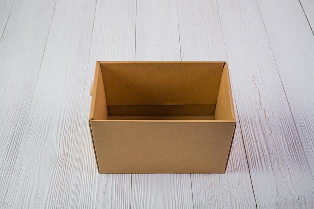 Braune pappschachtel oder behälter des leeren pakets auf hellem holztisch mit kopienraum. Premium Fotos
