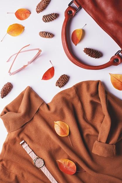 Braune strickjacke der frau mit ledertasche, mode-accessoires und herbstlaub Premium Fotos