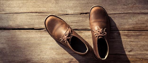 Braune stylische stiefel auf holz Premium Fotos
