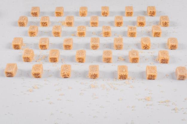 Braune zuckerwürfel mit hoher blickwinkel aufgereiht Kostenlose Fotos